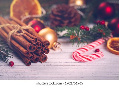 Christmas Holidays Composition Cinnamon and Christmas Decoration on White Wooden Background. New Year Concept and Christmas banner. Toned image. Selective focus.