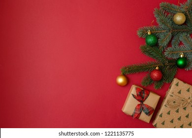 Christmas holidays composition on red background with copy space for your text. Xmas tree fir branches with ball, Christmas gift with bow. Xmas backdrop for greeting card. Flat lay, top view, overhead