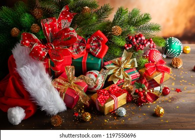 Christmas holidays composition with Santa Claus red hat, Christmas balls and gift boxes on wooden background