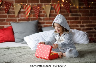 Christmas Holidays. Cute girl 8-9 years, sits on a bed with a box in his hands. She received a Christmas gift. Bedroom decorated with Christmas garlands. Children adore Christmas and Christmas gifts.