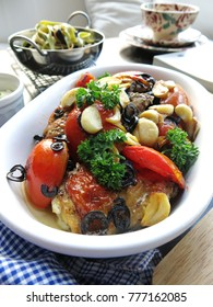Christmas or holidays food idea, roasted chicken with grilled tomato, garlic, black olive serve with pasta and Parmesan cheese.