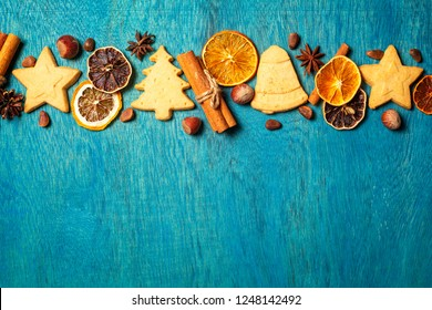 Christmas holidays ornament made from home made cookies and traditional festive spices on wooden blue background, flat lay with copy space