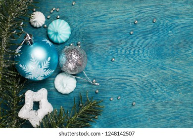 Christmas holidays ornament in white and blue colors on blue wooden background, top view