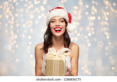 christmas, holidays and people concept - happy smiling young woman with red lipstick in santa hat holding present over festive lights background