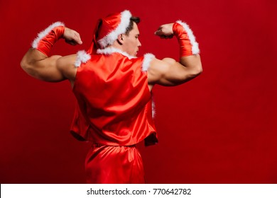 christmas holidays. sexy strong santa claus wearing hat. Young muscular man. torso, six pack fitness female. red background. copy space. Demonstrates the muscles of the biceps. Back view.
