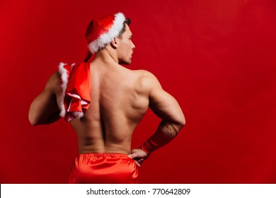 christmas holidays. sexy strong santa claus wearing hat. Young muscular man. torso, fitness female. red background. Demonstrates muscles of back view. striptease. vest over shoulder. profile.