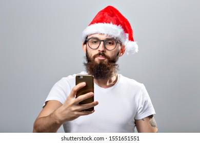 Christmas, holidays, technology and people concept - handsome bearded man in santa hat taking selfie picture with smartphone on grey background