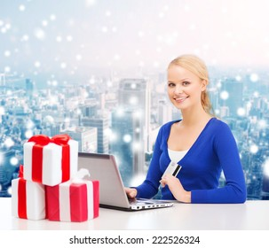 christmas, holidays, technology and shopping concept - smiling woman with gift boxes, credit card and laptop computer over snowy city background