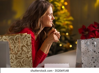 Christmas holidays are a time of gift-giving. Todo list can make Christmas season easy and save time for more fun.Happy young woman among shopping bags with pen and notebook thinking what's left to do