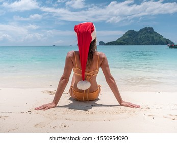 Christmas holidays in tropical paradise; Young woman in bikini wearing Santa hat sitting on white sand beach contemplating the seascape and Islands; Beach vacations, girl sunbathing