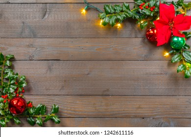 Christmas holly with ornaments, poinsettia, lights and berries on a wood background