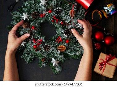 Christmas home decoration, female hands holding a wreath, hand made