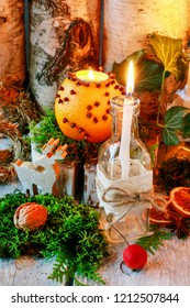 Christmas home decoration with pomander, candles, moss and paradise apples.