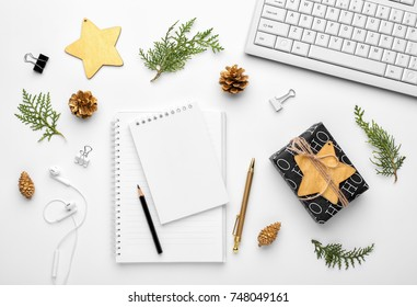 Christmas home office desk with computer, notebook, gifts, branches, christmas gold decorations. Flat lay, top view.