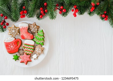 Christmas homemade gingerbread cookies and fir branches on white wooden background.