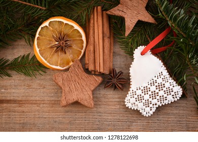 Christmas homemade gingerbread cookies on wooden background, dried oranges, cinnamon and spices. Winter baking cookies for christmas.