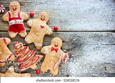 Christmas homemade gingerbread man and christmas tree cookies on snowy wooden table. Traditional cookies with icing and candy cane Christmas gift for kids