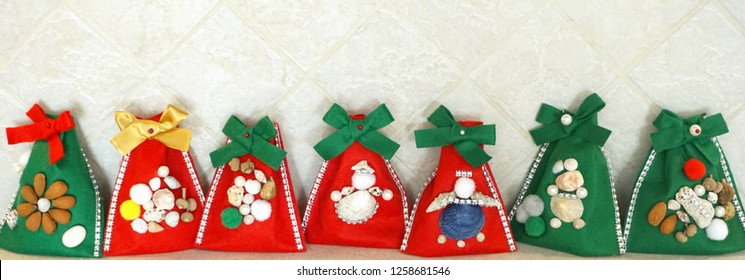 Christmas homemade green and red felt gift bags in line, decorated with little things