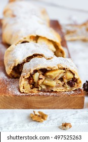 Christmas homemade pastry. Apple strudel (pie) with raisins, walnuts and powdered sugar with Christmas decor close up.