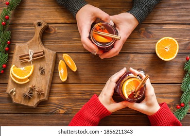 Christmas hot drink - mulled red wine in glass mug with spices and fruits in the hands of men and women. New Year decoration on a wooden background. Top view