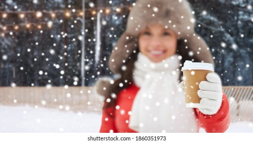 christmas, hot drinks and holidays concept - happy woman with disposable paper coffee cup in winter over outdoor ice skating rink on background