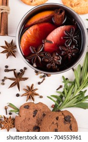christmas hot mulled wine with cinnamon cardamom and anise and cookies on white wooden background with christmas tree