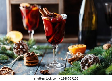 Christmas hot mulled wine in a glass with spices, citrus fruit and cranberry. Christmas atmosphere.