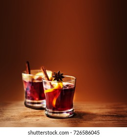 Christmas Hot mulled wine for winter with spices and orange slices on rustic table with copy space.  Red Hot wine or gluhwein with Christmas Decorations on wooden background, close up