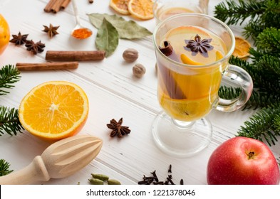 Christmas hot white mulled wine in glass with orange, honey, cinnamon sticks and star anise with spices and ingredients on white wooden background. Spicy warm beverage. Seasonal mulled drink.
