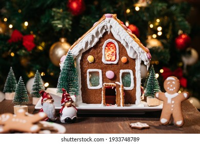 Christmas house from ginger cookies with ginger man outside decorated in Christmas spirit with tree in background