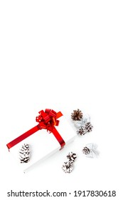 Christmas Ideas. White Giftbox Wrapped in Red Ribbon Together with Cones On White. Vertical Orientation