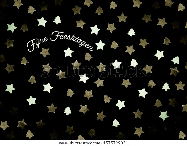 Christmas image with the Dutch words Fijne Feestdagen (translation: Happy Holidays). Stars and Christmas trees on a black background.