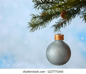 Christmas image of pine branch with small cones on blue tinted bokeh background. A sparkly blue ornaments hangs. Copy space