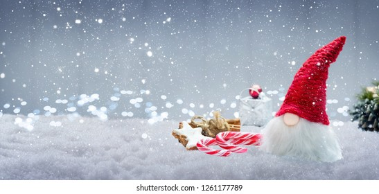 Christmas imp with sweets in the snow, banner