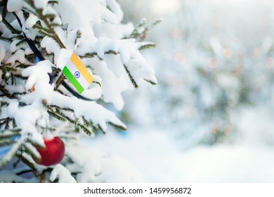 Christmas India. Xmas tree covered with snow, decorations and a flag of India. Snowy forest background in winter. Christmas greeting card.