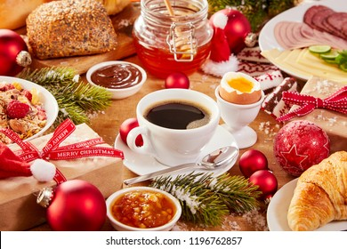 Christmas Intercontinental breakfast table with an assortment of tasty fresh food, coffee, gifts and colorful red decorations sprinkled with winter snow