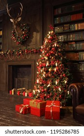 Christmas interior with bookshelves, stuffed deer, wooden fake fireplace, christmas tree, boxes in studio