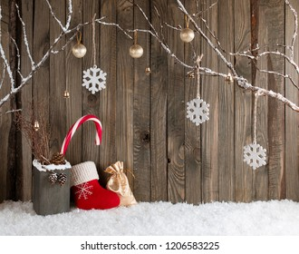Christmas interior with decorative branches, Santa boot, gift bag and candy canes on wooden planks background. New Year winter composition.