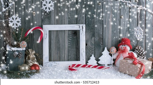 Christmas interior with snowman, photo frame, decorative branches, presents and candy canes on wooden planks background. New Year winter composition.