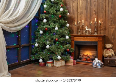Christmas interior with toys and lots of candles, wooden fake fireplace, christmas tree, boxes in studio