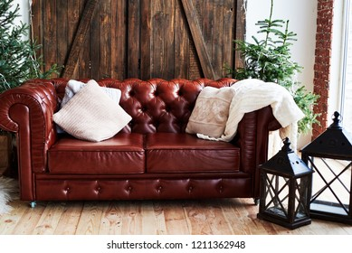 Christmas interior with vintage brown leather sofa and fir tree with gift boxes in loft room with wooden door decorated with Christmas wreath and garland, copy space