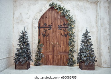 Christmas interiors. Christmas decorations on wooden doors. Christmas trees in bright room.