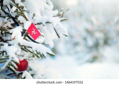 Christmas Isle of Man. Xmas tree covered with snow, decorations and a flag of Isle of Man. Snowy forest background in winter. Christmas greeting card.