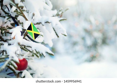 Christmas Jamaica. Xmas tree covered with snow, decorations and a flag of Jamaica. Snowy forest background in winter. Christmas greeting card.