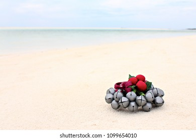 Christmas Jingle Bells Ornament on the Beach Sand, shallow focus