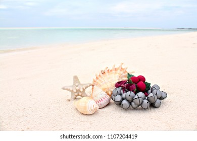 Christmas Jingle Bells Ornament on the Beach Sand, minimalist scene, shallow focus