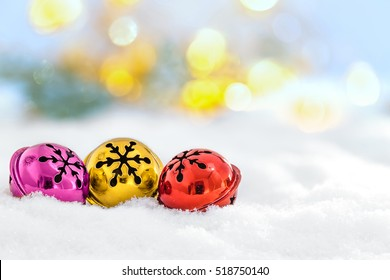 Christmas jingle bells in the snow and defocused lights