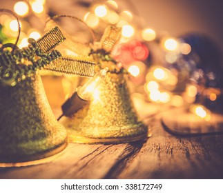 christmas , jingle golden bell deco with rusty gold light bulb on wood background with copy space