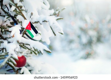 Christmas Jordan. Xmas tree covered with snow, decorations and a flag of Jordan. Snowy forest background in winter. Christmas greeting card.