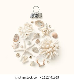 Christmas in July / at the beach / in the southern hemisphere concept with holiday ornament made of shells, starfish and corals on a cream colored background, flat lay / top view, copy space for text